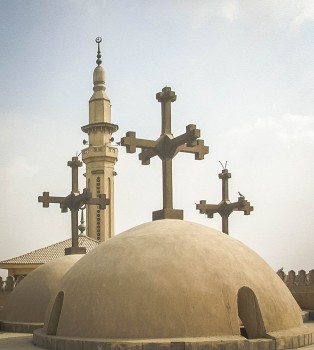 Photo: Paul Perry, a mosque's minaret seen through the domes of the Church of the Holy Virgin at Musturud. It is common to have a mosque close to a church.