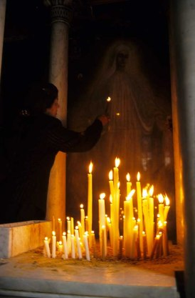 Photo: Norbert Schiller, a woman holds a candle before an icon of the Holy Virgin in the Church of the Holy Virgin at Zaytun.