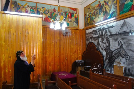 Photo: Shangyun Shen, Father Maximous checking a painting in the church, it depicts the Flight into Egypt.