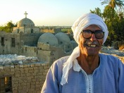 Photo: Paul Perry, an elderly Christian man on the roof of his house. behind him we can see the churches of St. Anthony the Great and the Church of Abu Sefein at Dayr Al-Maymun.