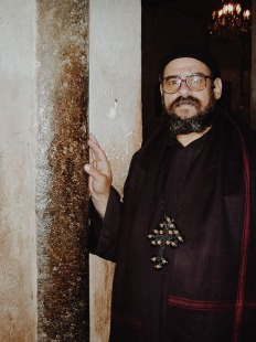 Photo: Paul Perry, father Girgis beside an ancient pillar of the old Church of Anthony. The ancient pillar has been almost entirely covered in concrete to support it.