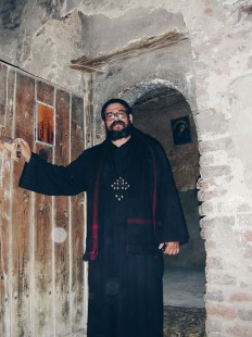 Photo: Paul Perry, father Girgis opening the ancient door leading to the Church of Abu Sefein at Dayr al-Maymun.
