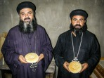 """Photo: Paul Perry, the two priests holding Eucharistic breads are brothers. The bread is leavened, unsalted made of the finest flour. The twelve crosses refer to the twelve disciples, and the five holes refer to the wounds of of crucifixion. We can also see the word """"Agios"""" or """"Holy"""" written on the bread three times symbolizing the Father, the Son, and the Holy Spirit."""