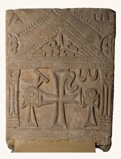 "Photo: The Coptic Museum, tombstones from the early years of Christianity are often decorated with an architectural structure symbolizing the house of God. Various Christian symbols fill the lower part of this gravestone. In the centre is Christ's monogram, comprising the two Greek letters ""Chi"" and ""Rho"". This monogram is the most common symbol of Jesus along with the cross and fish. Here it is flanked by looped crosses (crux ansata), formerly the Egyptian Hieroglyph ""Ankh"" (the key of life), and the first and last letter of the Greek alphabet ""Alpha"" and ""Omega"", evoking eternity. All of these Christian signs are framed by fluted columns. Two leaves and a Greek inscription are set inside the pediment. The inscription gives the deceased's name, the date of his death and expresses the wish that he may ""rest in peace""."
