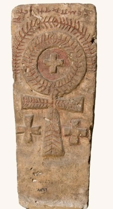 "Photo: The Coptic Museum, this gravestone is carved with a looped cross, formerly the Egyptian ""Ankh"" (the Pharaonic key of life). It is decorated with a wreath-like pattern and flanked by Greek crosses. Another Greek cross is set inside the loop which is surrounded by a palm branch, which symbolises victory."