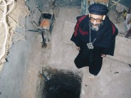 Photo: Paul Perry, priest standing near the blessed well in the church of Buq.